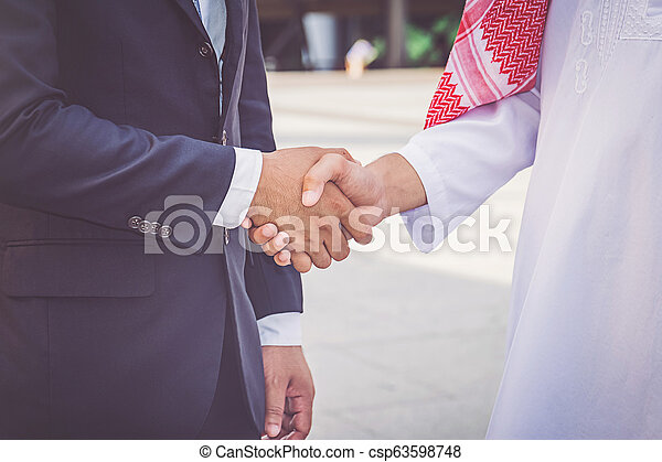 Arabic businessman giving an handshake to his business partner, on construction site - csp63598748