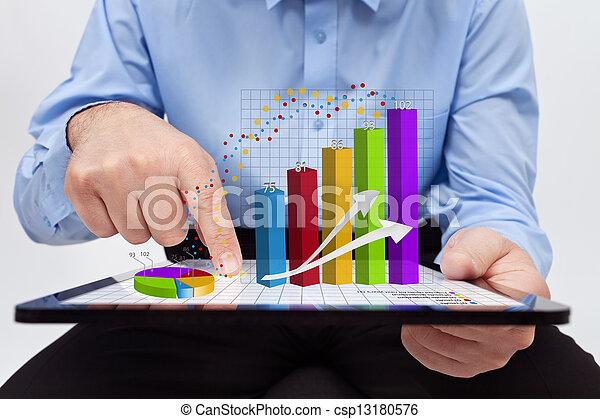 Geschäftsmann, der an Jahresberichten arbeitet, nähert sich den Charts - csp13180576