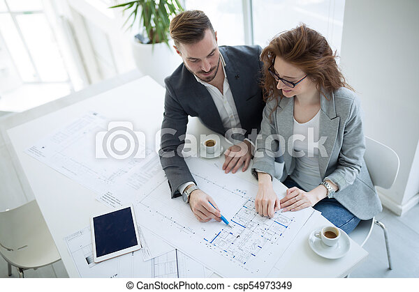 Architect colleagues working in office - csp54973349