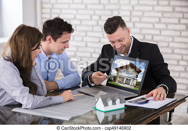 Architect Showing House Model To Couple In Office - csp49146902