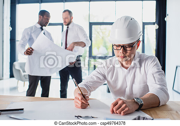 architect working on new project with colleagues behind in modern office - csp49764378