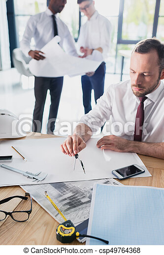 architect working on new project with colleagues behind in modern office - csp49764368