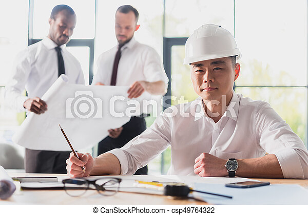architect working on new project with colleagues behind in modern office - csp49764322