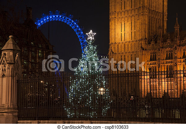 Architectural detail of Houses of Parliament in London England with Christmas tree in foreground and London Eye in background - csp8103633