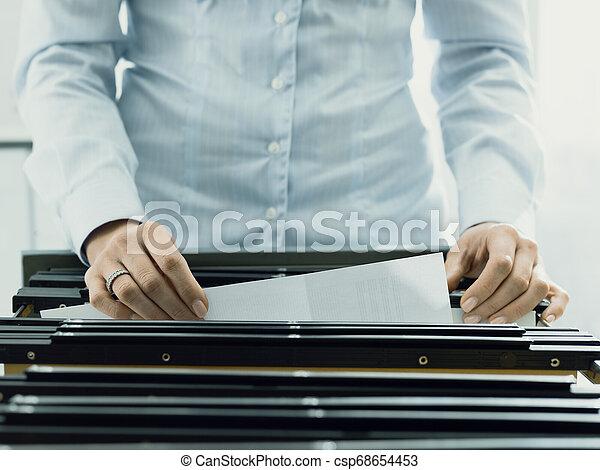 Trabajador de oficina buscando archivos en el archivo - csp68654453