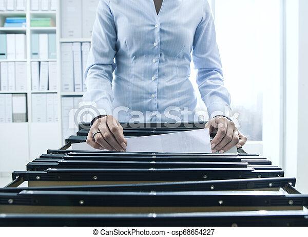 Trabajador de oficina buscando archivos en el archivo - csp68654227
