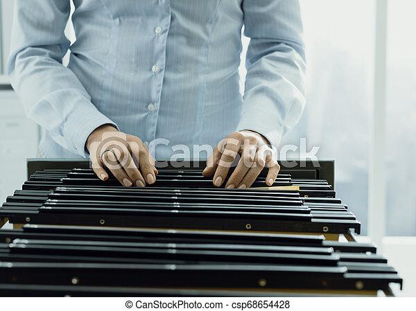 Trabajador de oficina buscando archivos en el archivo - csp68654428