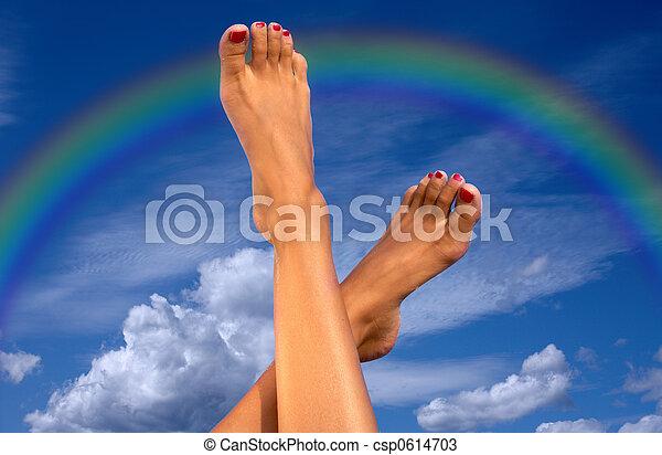 Piernas sobre el cielo con nubes y arco iris - csp0614703