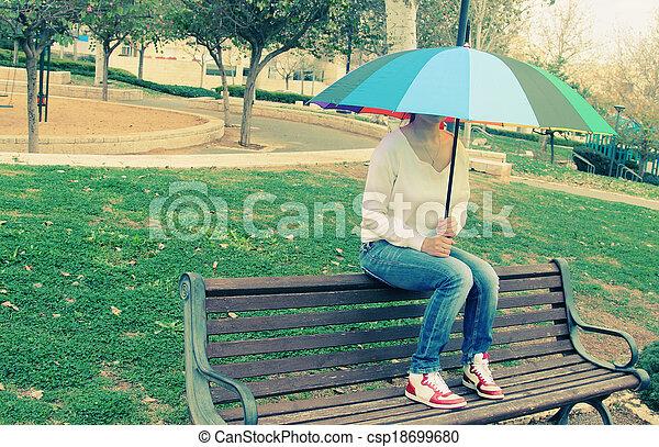 Una joven sentada bajo un gran paraguas arcoíris - csp18699680