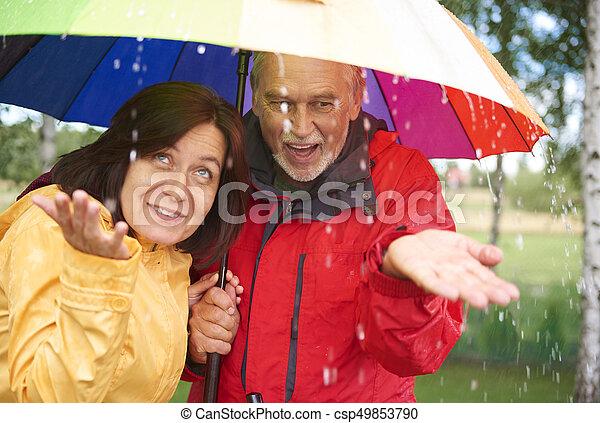 Una pareja mayor bajo el paraguas arco iris atrapando gotas de lluvia - csp49853790