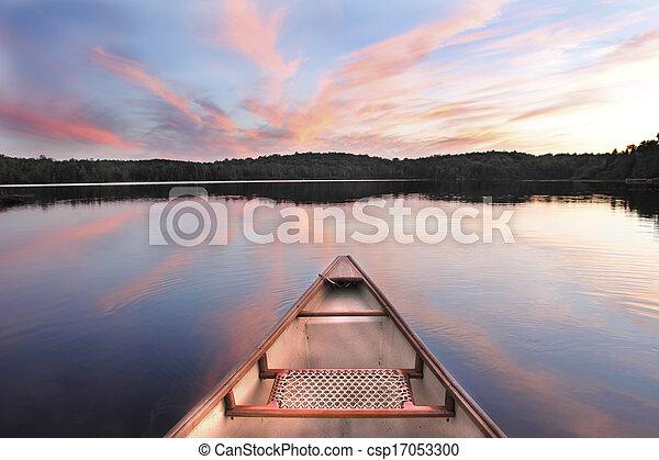 La canoa se inclina sobre un lago al atardecer - csp17053300