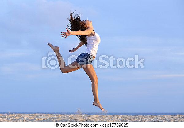 Mujer saltando en la arena de la playa - csp17789025