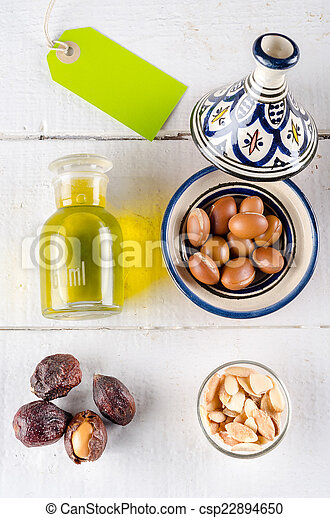 Argan nuts and oil on white wooden tabletop with green label - csp22894650
