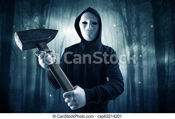Armed hitman in dark nocturnal forest concept - csp63214201