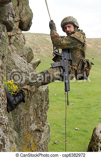 Armed military alpinist hanging on rope - csp6382972
