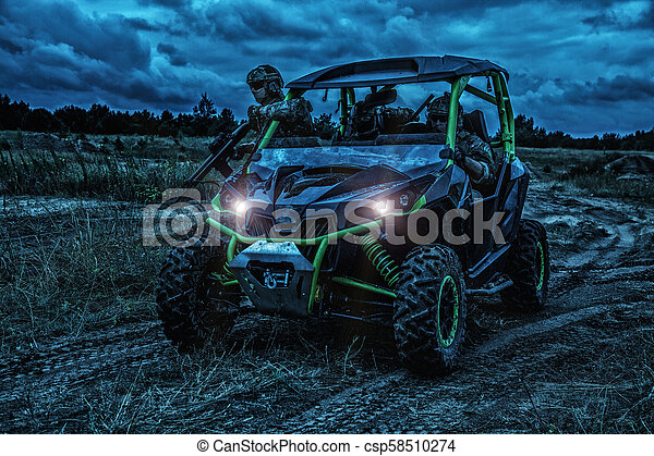 Army rangers moving on military buggy at night - csp58510274