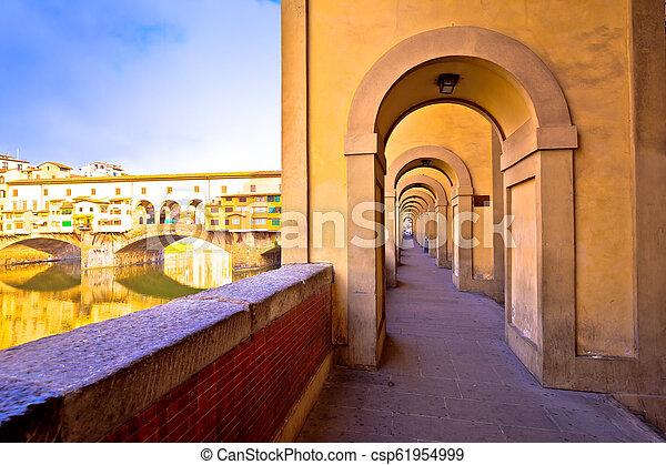 Arno river coastline and Ponte Vecchio bridge in Florence view - csp61954999