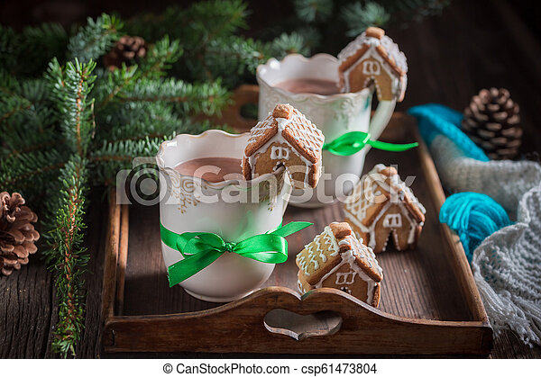 Aromatic gingerbread cottages with sweet drink for Christmas - csp61473804