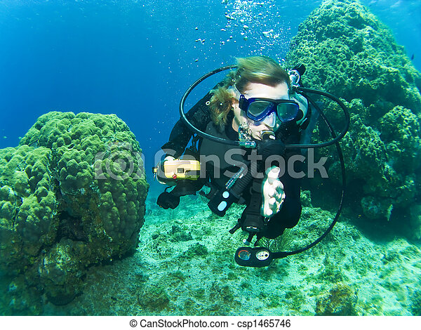 Un buceador femenino nadando entre el arrecife - csp1465746