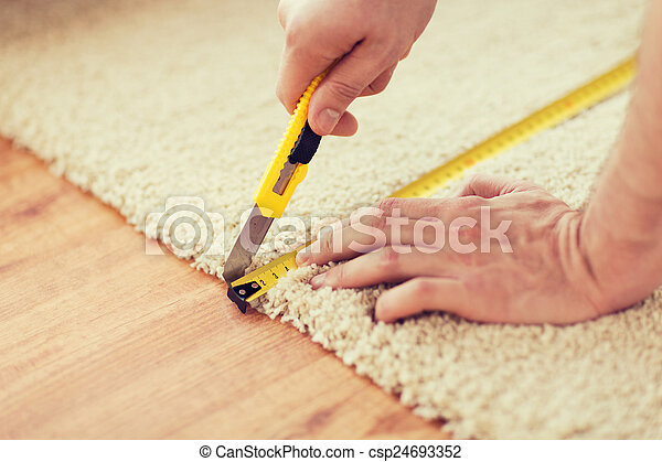 Un cierre de manos masculinas cortando alfombras - csp24693352