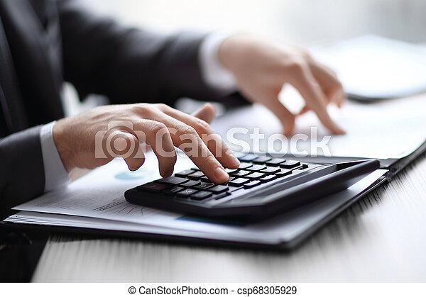 Cierra. El empresario comprueba los datos financieros con la calculadora - csp68305929