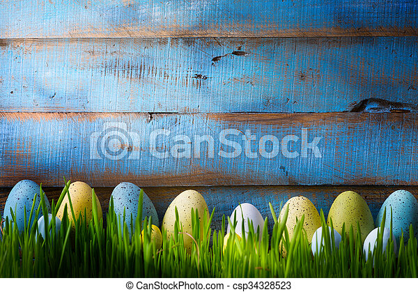 art Colorful easter eggs. Background with easter eggs on green grass - csp34328523