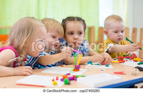 Grupo de niños haciendo artes y artesanías en la guardería - csp37455283