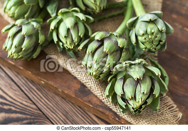 Artichoke bouquets on sackcloth on wooden background - csp55947141