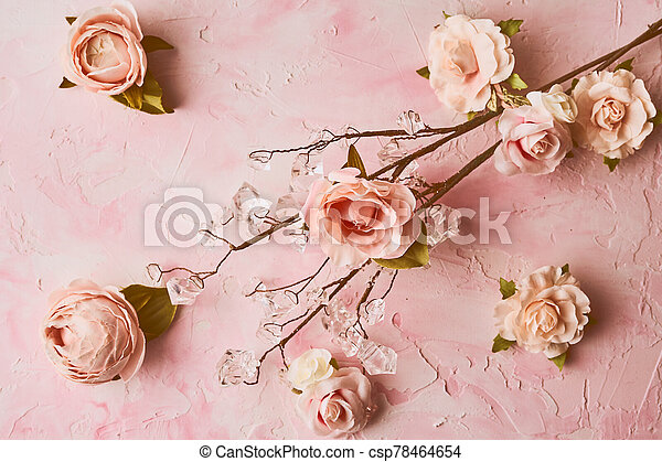 Artificial pink flowers arrangement on pink colored background - csp78464654