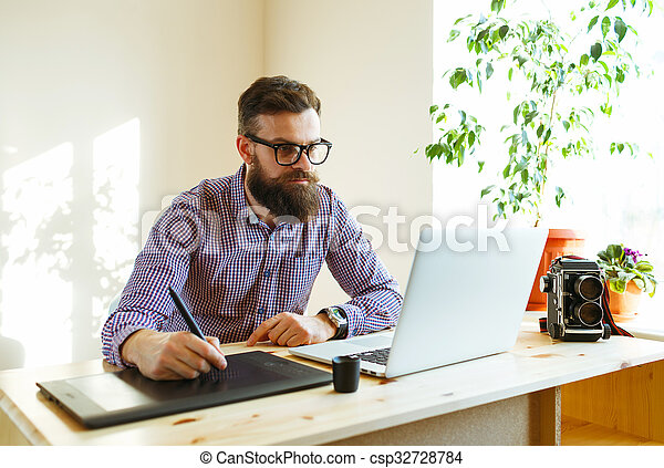 Artist drawing something on graphic tablet at the home office - csp32728784