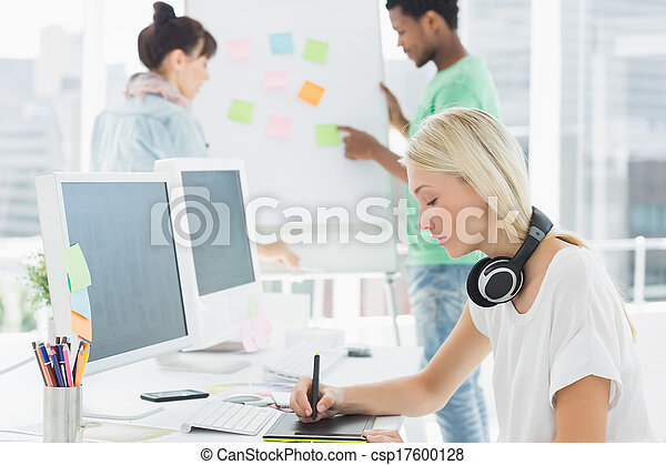 Artist drawing something on graphic tablet with colleagues  - csp17600128