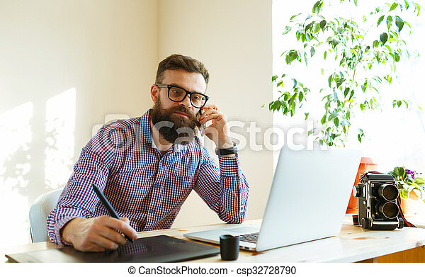 Artist drawing something on graphic tablet at the home office - csp32728790
