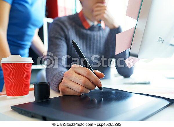 Artist drawing something on graphic tablet at the home office - csp45265292