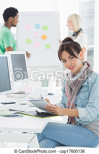 Artist drawing something on graphic tablet with colleagues  - csp17600136