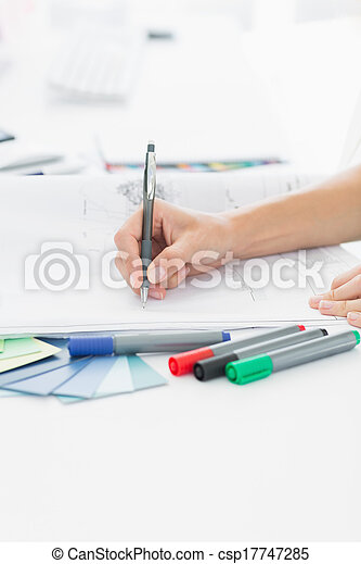 Artist drawing something on paper with pen at office - csp17747285
