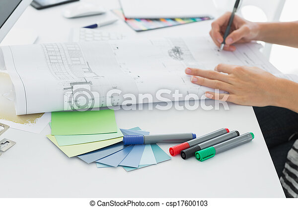 Artist drawing something on paper with pen at office - csp17600103