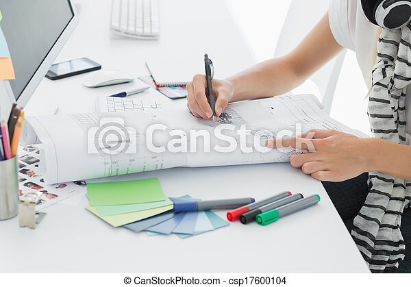 Artist drawing something on paper with pen at office - csp17600104