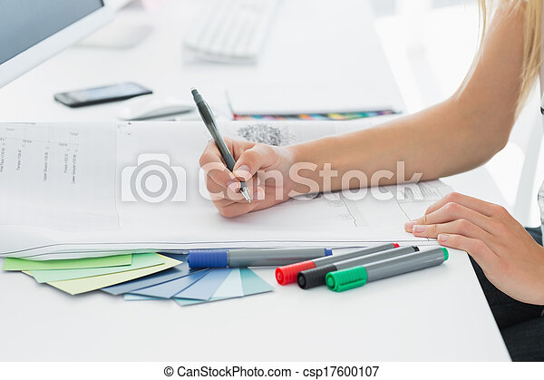 Artist drawing something on paper with pen at office - csp17600107