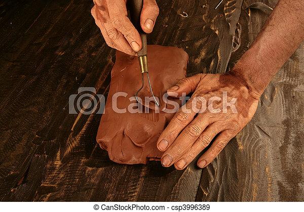 artist man hands working red clay for handcraft - csp3996389