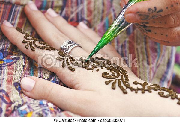 Artist painting traditional indian henna tattoo on woman hand