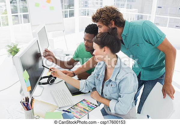 Tres artistas trabajando en la computadora de la oficina - csp17600153