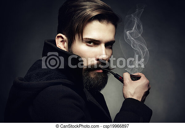 Artistic dark portrait of the young beautiful man. The young man smokes a tube. Close up - csp19966897