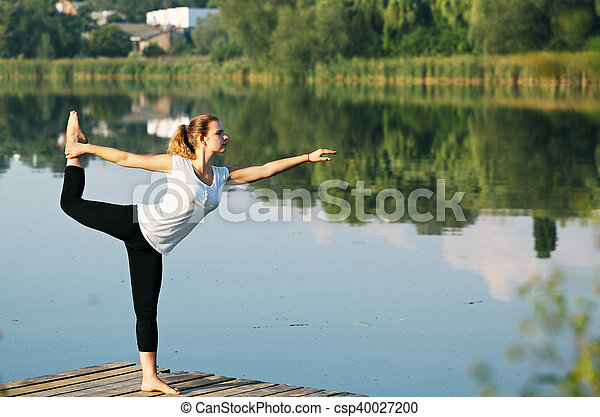 young beautiful woman engaged in yoga on the river bank
