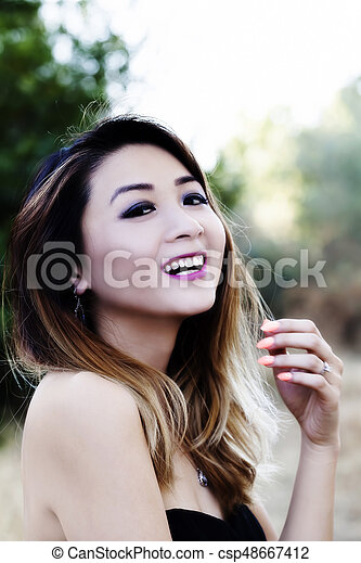 Asian American Woman Outdoors In Bare Shoulder Dress Smiling - csp48667412