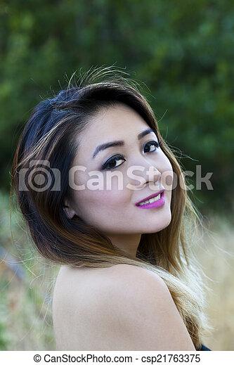 Asian American Woman Outdoors Portrait Bare Shoulders - csp21763375