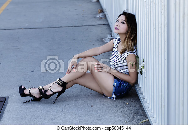Asian American Woman Sitting In Jean Shorts And Top - csp50345144