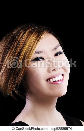 Asian American Woman Smiling Portrait Against Dark Background - csp52889974
