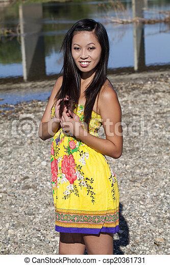 Asian American Woman Standing Outdoors Yellow Dress - csp20361731