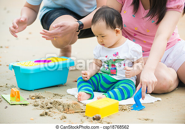 asian baby playing sand on the beach with father and mother - csp18768562