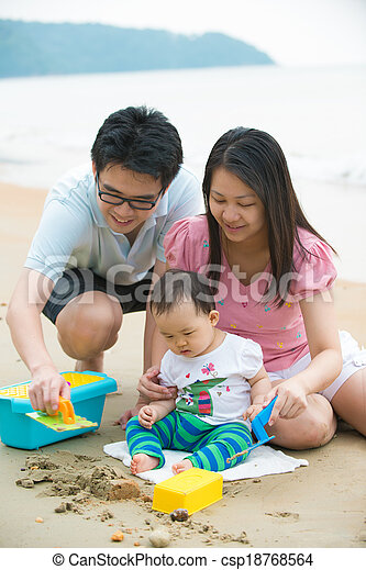 asian baby playing sand on the beach with father and mother - csp18768564